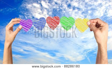 Woman And Man Hands Holding Paper Hearts Over Blue Sky
