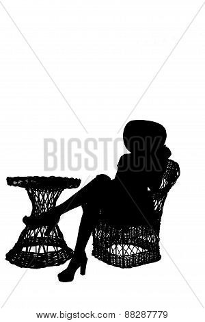 Silhouette Of Girl Sitting On Wicker Furniture