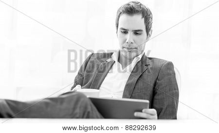 Pensive Young Business Executive With His Feet On The Desk
