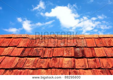 Rusty Tiles Of Old Roof Over Blue Sky