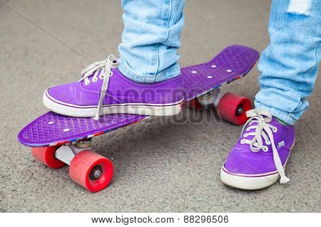 Young Skateboarder In Gumshoes And Jeans Stands