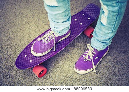 Young Skateboarder In Gumshoes And Jeans