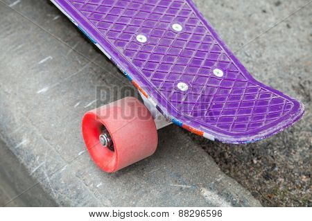 Modern Skateboard Stands On The Curb