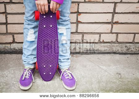 Teenage Girl In Jeans And Gumshoes Holds Skateboard