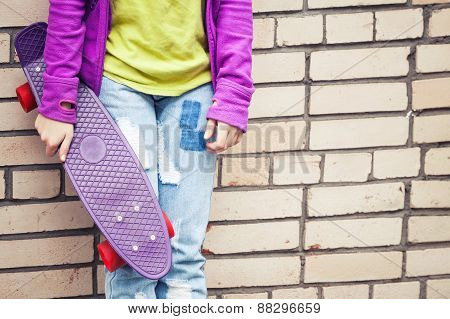 Blond Teenage Girl In Jeans Holds Skateboard