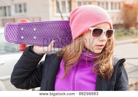 Teenage Girl In Sunglasses With Skateboard