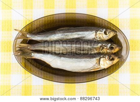 Few Smoked Fish In Glass Dish On Tablecloth
