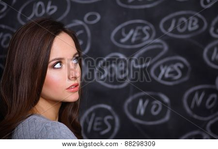 Thinking young woman with yes or no choice on grey background