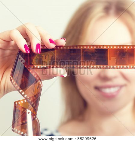 Smiling woman with photographic film in the hands.