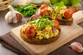 picture of scrambled eggs  - Scrambled eggs on toasted bread with bacon herbs and tomato poached in balsamic reduction