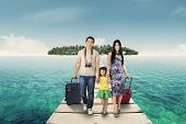 stock photo of carry-on luggage  - Happy family arriving at the resort and walking on the bridge while carrying their baggage - JPG