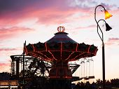 stock photo of carnival ride  -  a fair ride at dusk toned with a retro vintage instagram filter effect  - JPG