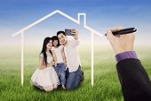 stock photo of dream home  - Little happy family taking self photo together on the meadow under a dream home - JPG