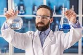 pic of scientist  - Handsome male scientist researcher in safety glasses observing liquid in flasks in a laboratory - JPG