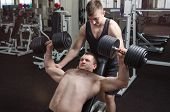 image of bench  - Young muscular man performs an exercise dumbbell bench press on an incline bench with a partner that it insures - JPG