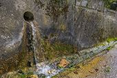 pic of gutter  - Water trickling in a sunny gutter next to a road - JPG