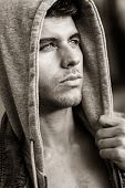 picture of hoods  - Good looking young man with blue eyes in the street wearing hooded jacket - JPG