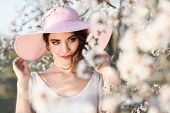 foto of flower girl  - Portrait of young woman in the flowered field in the spring time. Almond flowers blossoms. Girl wearing white dress and pink sun hat ** Note: Soft Focus at 100%, best at smaller sizes - JPG