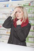stock photo of methadone  - Woman in pharmacy with headache and temperature - JPG
