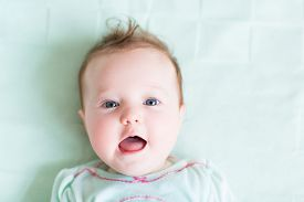 pic of mint-green  - Adorable Baby Girl In A Green Shirt On A Green Knitted Blanket Smiling - JPG