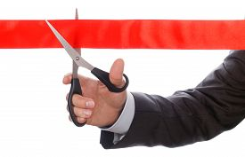 picture of pompous  - Hand of businessman in suit cutting red ribbon with pair of scissors isolated on white background - JPG
