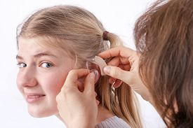 stock photo of insert  - Doctor inserting a hearing aid into a young girl - JPG