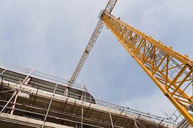 pic of tatas  - A view looking up to yellow tower crane on a construction site with concrete and steel structure - JPG