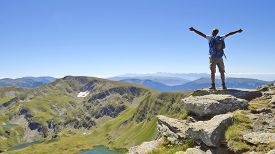 picture of mountain-high  - Male hiker in Rila mountains Bulgaria with arms stretched out to enjoy the mountain scenery - JPG