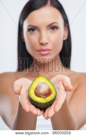 Cheerful young girl is showing exotic fruit