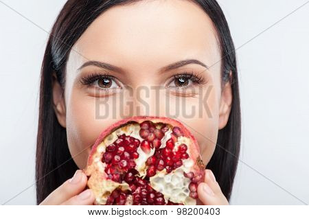 Attractive young woman is making fun with exotic fruit