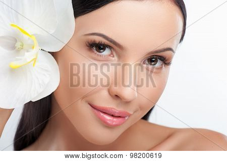 Beautiful young woman is playing with orchid