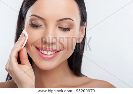 Cheerful young woman is cleaning her face