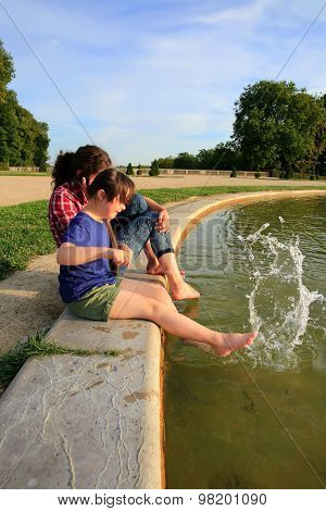 Young Girls Playing With The Fountain