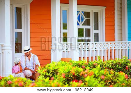 Cute Father And Son Sitting And Talking On Porch, Caribbean Street