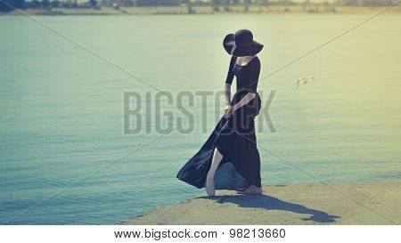 Ballerina In Hat And Black Dress Dancing On Riverbank. Toning.