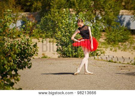 Ballerina In Red Tutu Dancing In Park.