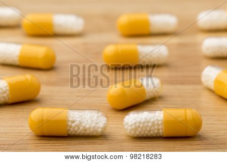 Close up medical capsules on wooden table
