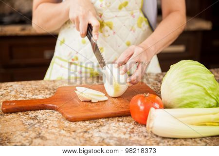 Cutting An Onion In A Chopping Board