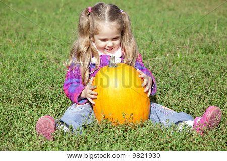 Little gardener girl with pumpkin at green grass