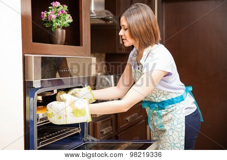 Woman Grabbing A Cake With Oven Mitts