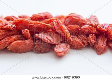 Goji berries are on white surface, macro