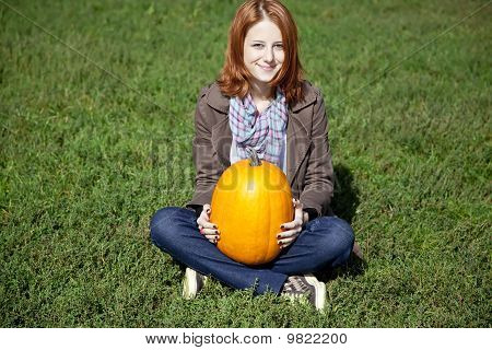 Young Women Sitting At Green Grass And Keeping Pumpkin.