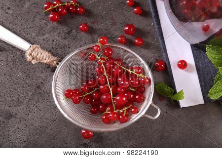 Ripe red currants in sieve on table, closeup