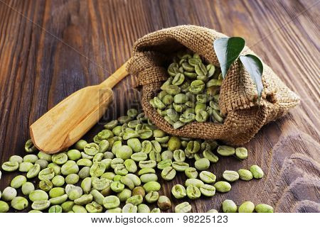 Green coffee beans with leaves and spoon in bag on wooden table close up