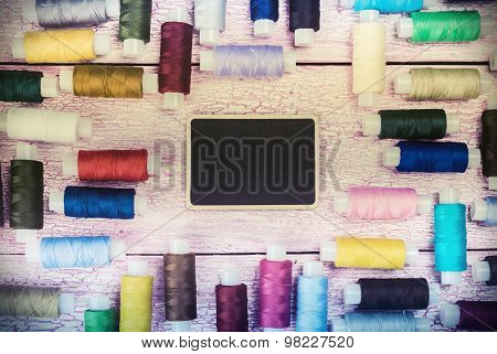 Bobbins With Colorful Threads On Old Wooden Table