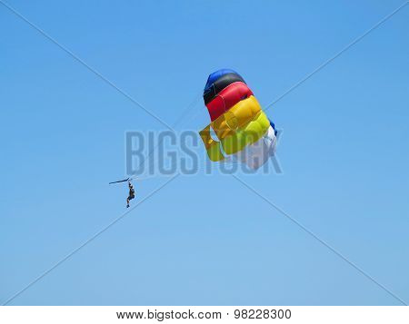 Parachutist Skydiver On Colorful Parachute And Blue Sky Background
