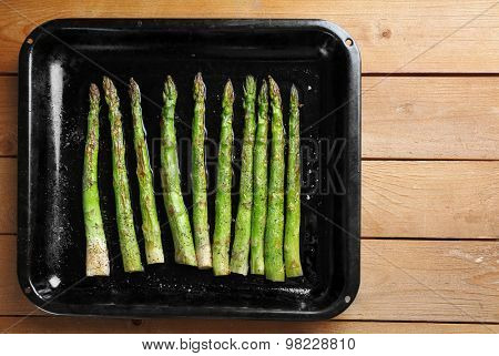 Roasted asparagus on pan, close-up, on table background