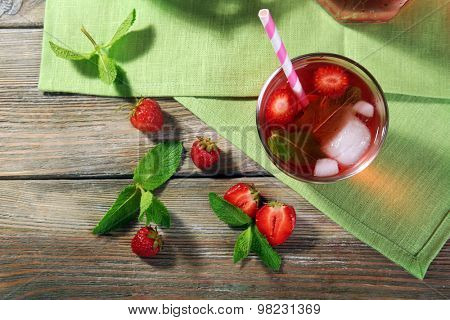Glass of strawberry juice with berries on table close up