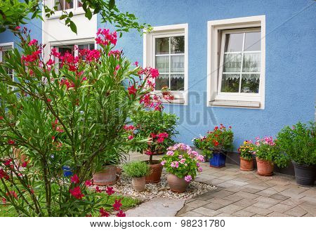 Blue House Front With Decorative Mediterranean Flower Pots