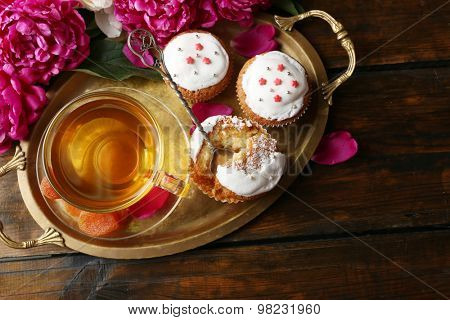 Composition with cup of herbal tea, dried apricots and peony flowers on wooden background